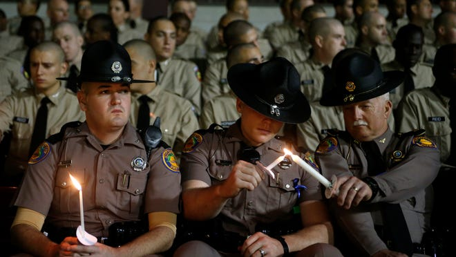 Community members and law enforcement officials gathered at Dick Howser Stadium on Monday for a vigil to celebrate the life of Deputy Chris Smith who was killed in the line of duty Saturday.