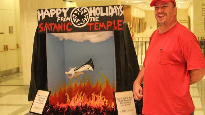 Satanic Temple member John Porgal smiles next to the group's holiday display set up in the Florida Capitol Monday.
