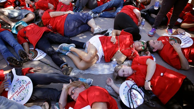 Nurses protest by pretending to be dead along Las Vegas Boulevard, Wednesday, Sept. 24, 2014, in Las Vegas. Nurses in town for the California Nurses Association and National Nurses Organizing Committee convention protested on the Strip because they say U.S. hospitals aren't ready for an Ebola outbreak. (AP Photo/John Locher)