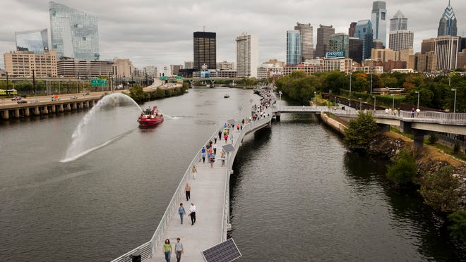 A Philadelphia Fire Department boat makes a water display as pedestrians and cyclist move along the Schuylkill Banks Boardwalk, Oct. 2 in Philadelphia.