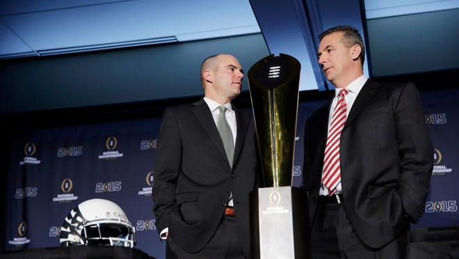 Ohio State head coach Urban Meyer, right, and Oregon head coach Mark Helfrich pose with the championship trophy after a news conference Sunday. Oregon plays Ohio State in the championship game today.
