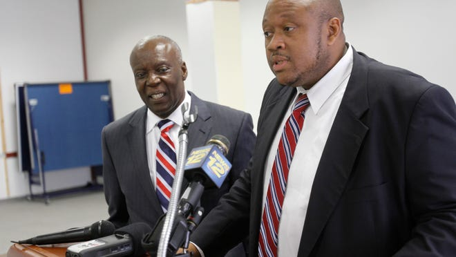 Spring Valley Village Attorney Jerrold Miles, along with Mayor Demeza Delhomme, address reporters at a press conference in July 2014.