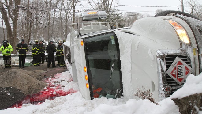 Bedford Hills firefighters work at the scene of a oil tanker truck rollover on Bedford Center Road near Broad Brook Road in Bedford Hills Feb. 2, 2015. There were no injuries but the truck contained 3200 gallons of home heating oil that was leaking onto the roadway. The Westchester County Haz-Mat Team was called in to assist.