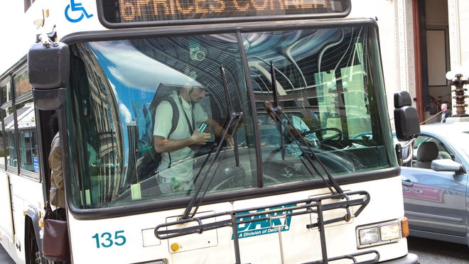 A passenger pays of his ride on a DART in Rodney Square, Wednesday. The transit agency soon will have meetings to outline several proposed route changes.  The final changes will go in effect January 2015.