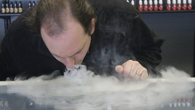 """Jason Mattison, above, """"vapes"""" at his new store in Wisconsin Rapids."""