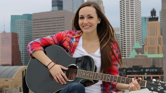 Karina Kern poses with her guitar against the Minneapolis skyline in a photo shoot for her debut EP.