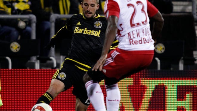 Columbus Crew midfielder Ethan Finlay, left, passes the ball in front of New York Red Bulls defender Ronald Zubar during the first leg of the MLS soccer Eastern Conference championship in Columbus, Ohio, Sunday, Nov. 22, 2015. The Crew won 2-0. (AP Photo/Paul Vernon)