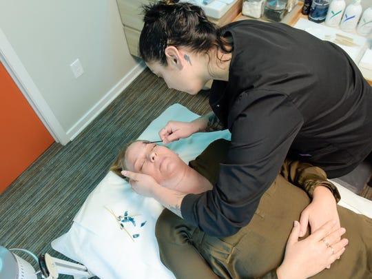 Melanie Knobel has her eyebrows waxed by Kur Wellness Studios employee Jessica Roszkowski.