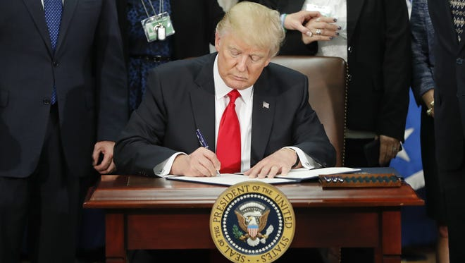 President Donald Trump signs an executive order for border security and immigration enforcement improvements at the Department of Homeland Security in Washington Jan. 25.