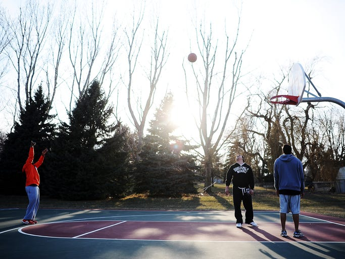 Yohanes Belay, left, takes a shot while Ressul Ajdari, center, and Nick Arrington, right, look on while playing basketball on Saturday evening, April 5, 2014, at Lions Centennial Park in Sioux Falls. According to the National Weather Service in Sioux Falls, the high on Saturday was 57 degrees, with Sunday's high projected to be 60 degrees. (Joe Ahlquist / Argus Leader)
