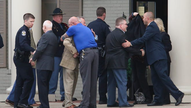 Mourners greet one another outside the Arch L. Heady at Resthaven Dignity Memorial as they attended the visitation for Officer Nick Rodman who died in a collision in his patrol car last week.  Apr. 3, 2017