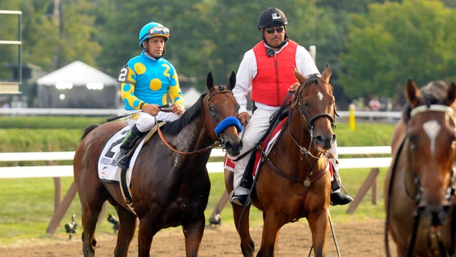 Triple Crown winner American Pharoah, left, with Victor Espinoza is led off the track after losing to Keen Ice in the Travers Stakes.