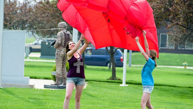 Clear Lake resident Elizabeth Brandt, left, and her sister, Katherine help get a pilot kite into the air on May 7, 2016, during the Kites on the Green festival at Johnston Public Library.