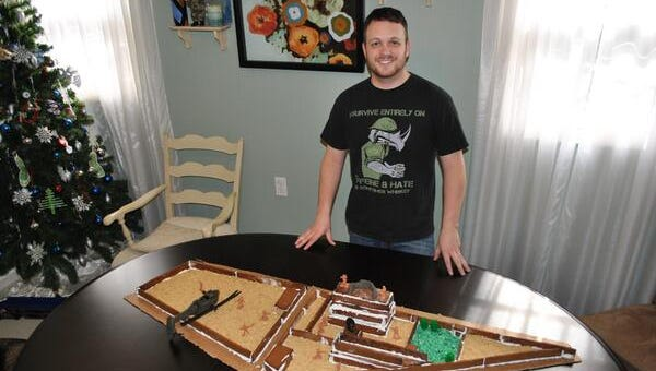 Steve, an Army military intelligence officer,  displays his gingerbread house model of Osama bin Laden's compound.