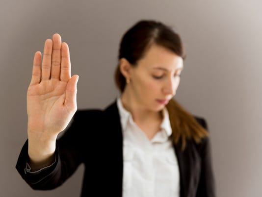 Woman in business suit showing her palm, body language, say NO at work, self-awareness