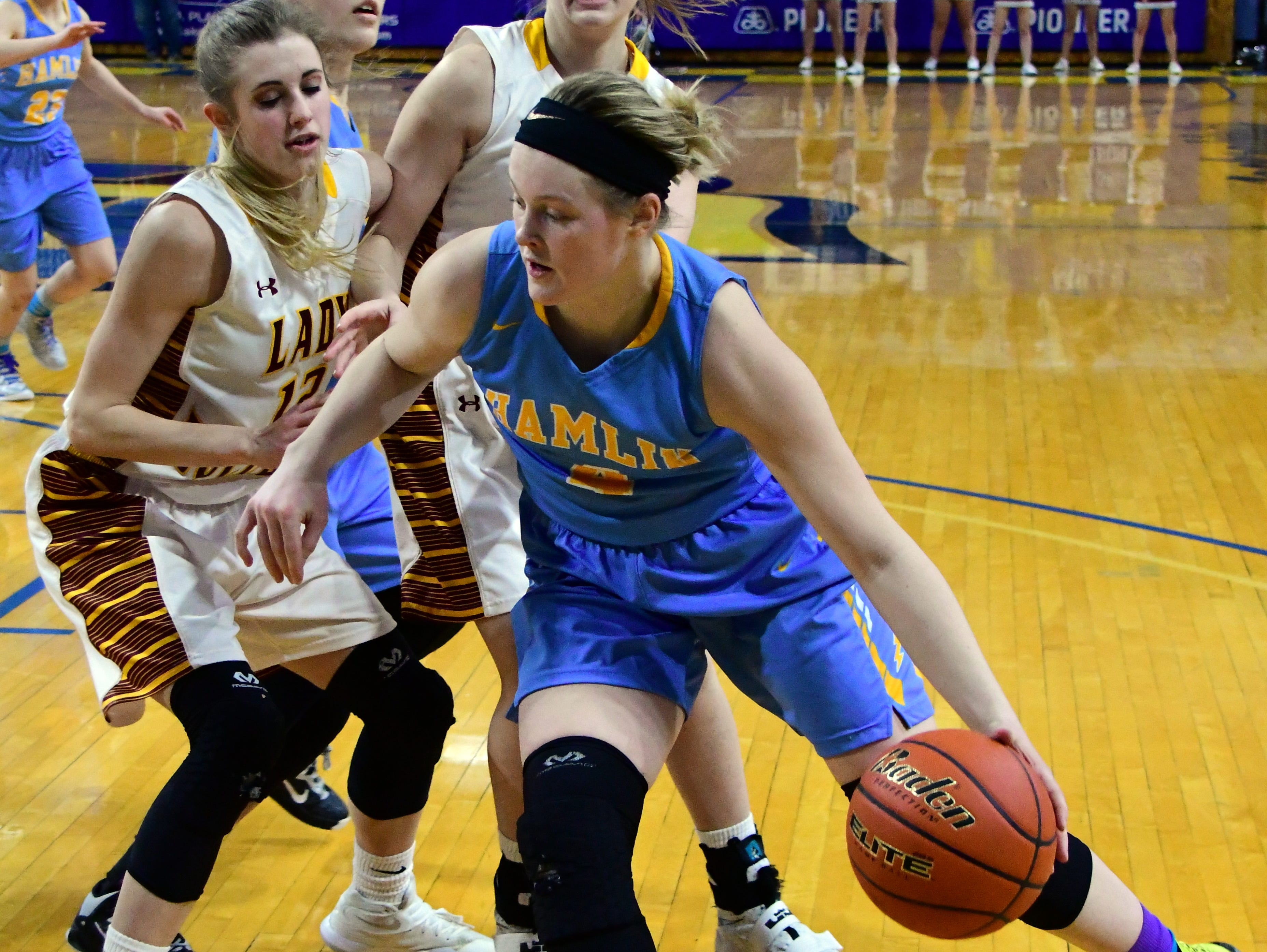 Hamlin's Lexi Wadsworth drives around a pair of Madison defenders during the Class A girls 5th place game.
