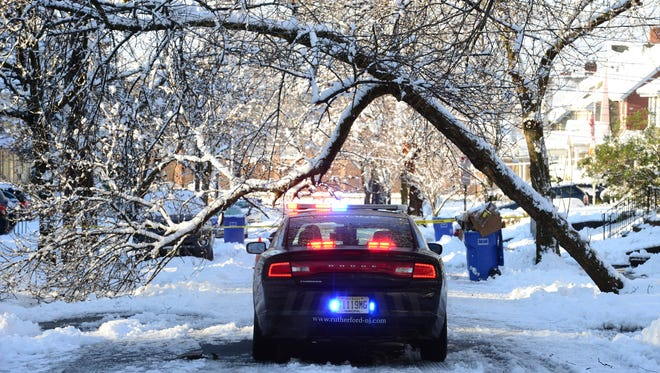 A Rutherford Police Officer has been waiting through the night for PSE&G to arrive on Wheaton Place to address a fallen tree leaning on live wires in Rutherford on Thursday morning March 8, 2018.