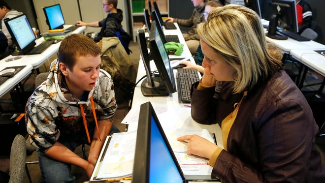 Shelbi Fortner helps Ethan Irons, 14, review his geometry homework at Clinton County Learning Network in Frankfort. A science teacher at Frankfort High School, Fortner also works as a tutor to supplement her income. Rep. Sheila Klinker, D-Lafayette has authored a bill to increase teacher pay.