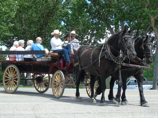 A horse-drawn wagon delivers members of the Valier
