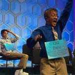 Dev Jaiswal of Louisville waves to supporters from the stage of the Scripps National Spelling Bee.