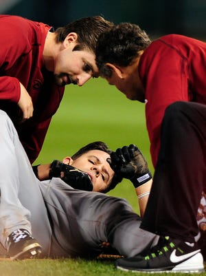 Diamondbacks catcher Tuffy Gosewisch is looked at by trainers after running to first in a game at St. Louis on May 27, 2015.