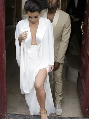 (FILES) - A picture dated May 23, 2014 shows US reality TV star Kim Kardashian (L) and singer Kanye West (R) leaving their residence in Paris ahead of their wedding. Kanye West and Kim Kardashian have caught the world's paparazzi off-guard by choosing to secretly honeymoon in the rain-sodden Irish countryside, according to media reports on May 26, 2014. AFP PHOTO / KENZO TRIBOUILLARDKENZO TRIBOUILLARD/AFP/Getty Images ORG XMIT: 702 ORIG FILE ID: 530150993