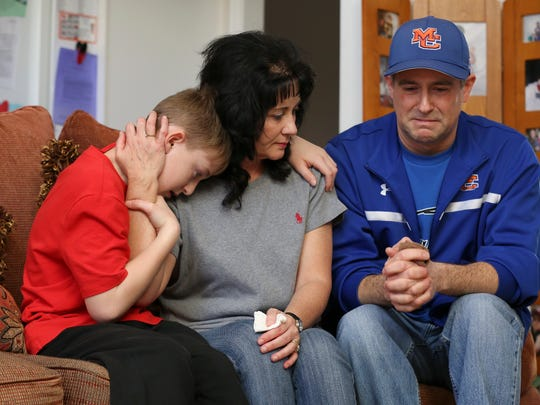 Brian Cope, right, became emotional as he talked about his son Preston Cope, 15, who was shot and killed during a shooting at Marshall County High School this week.  His wife Teresa Cope and their other son Maddox Cope, 11, left, embraced.