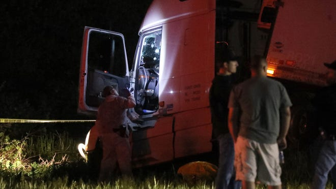 Deputies check over a truck where multiple bullet holes could be seen in the driver's side windshield in May after a truck driver fled police and shot several times at them before being killed in Geneseo. Federal agents found multiple explosive devices, firearms and cash at a property the driver rented in Virginia.