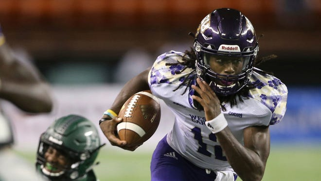 Western Carolina quarterback Tyrie Adams (12) runs through the Hawaii defense during the second quarter of an NCAA college football game, Saturday, Sept. 2, 2017, in Honolulu. (AP Photo/Marco Garcia)