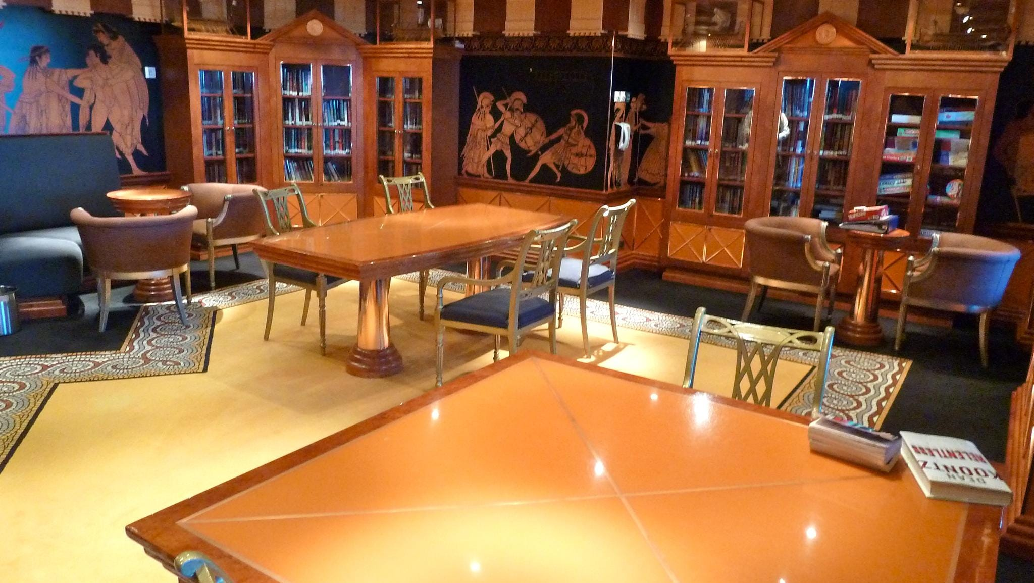 The 17-seat Iliad Library is adjacent to the Atrium America on Deck 4. Highlights include mosaic floors and artwork simulating scenes depicted on ancient Greek pottery shards.