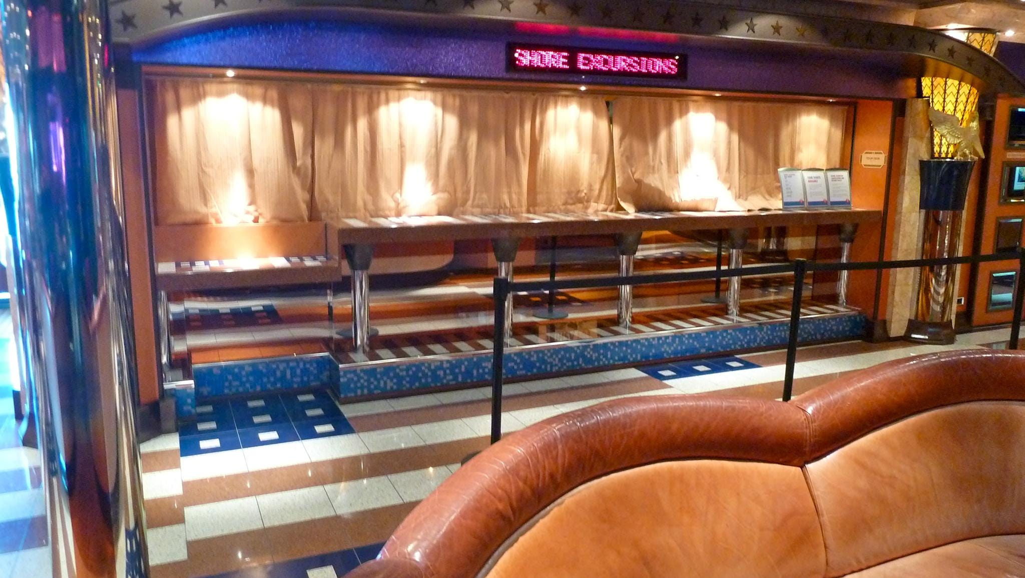 Across from Guest Services, there is the Shore Excursions desk.