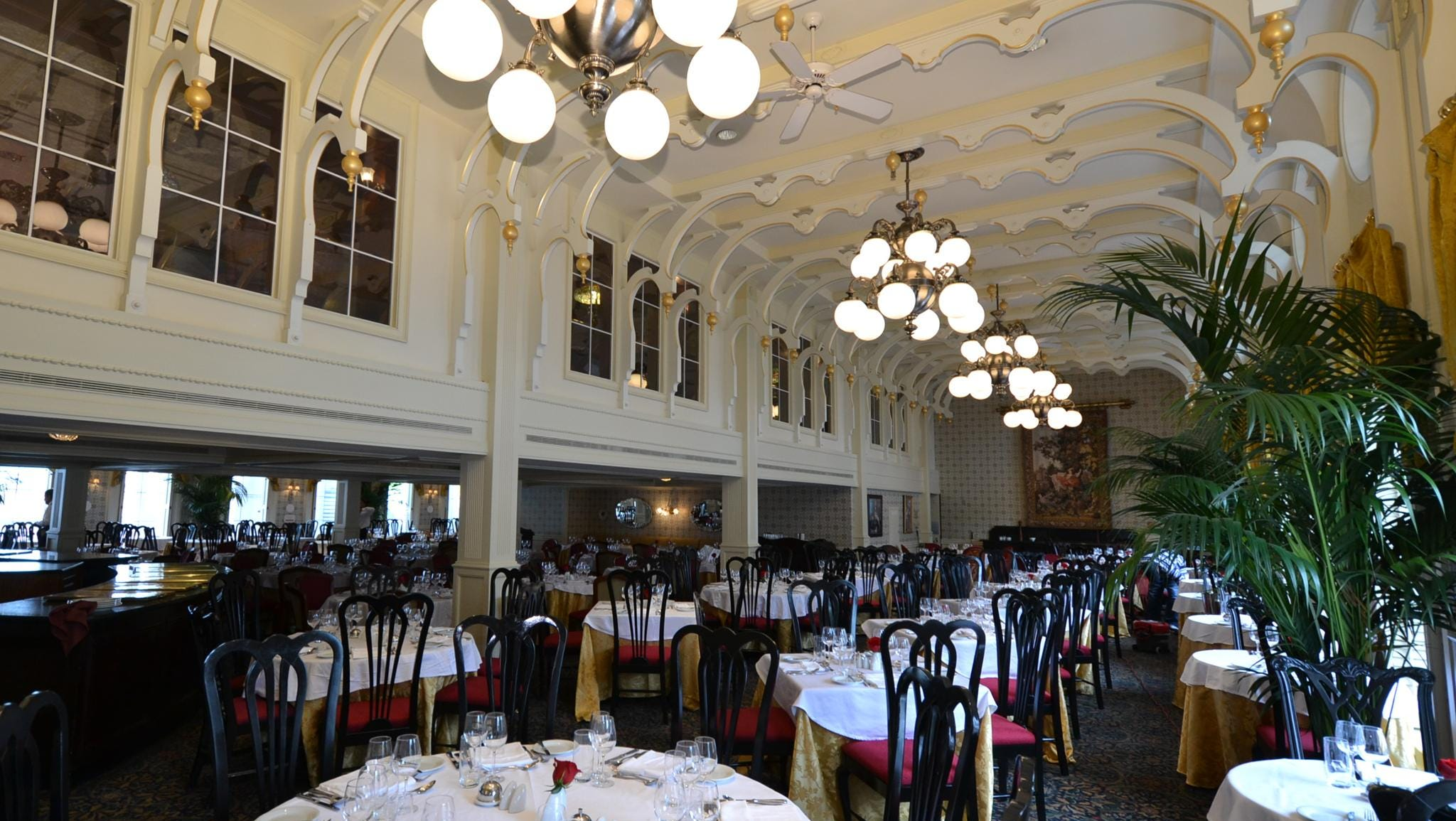 The ceiling of the American Queen's J.M. White Dining Room soars two stories in places and has large windows that look out to the rivers on which the American Queen sails.