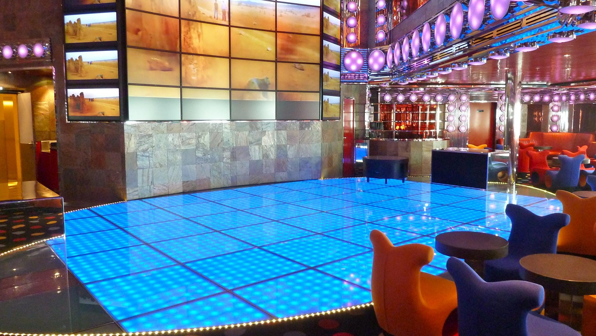 "Inboard of the Lounge and Bar Alcazar on Gardenia Deck, there is the lower level of the double-deck Discoteca Shaharazad (Farsi and Arabic for ""city dweller""), which features a fiber-optic acrylic dance floor, vivid polka dots and pulsating lavender and blue lighting."