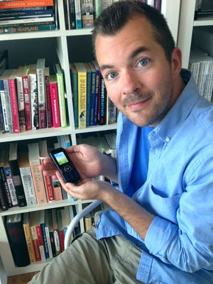 """Raygun founder Mike Draper with his """"dumb phone."""""""