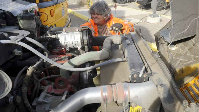 Driver Cheri Glancy checks the oil in her bus before heading out on a route.