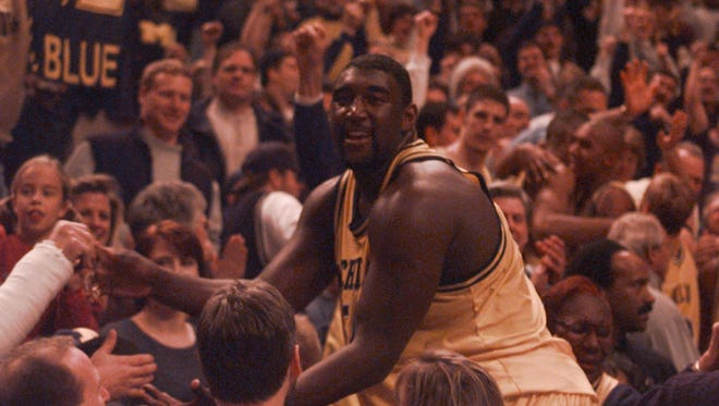 Michigan big man Robert Traylor heads into the stands to celebrate with fans after the Wolverines beat Purdue to win the first Big Ten basketball tournament championship on March 8, 1998.