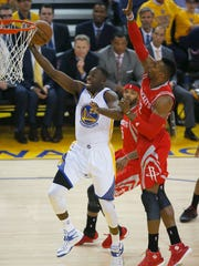 Golden State Warriors forward Draymond Green shoots against Houston Rockets center Dwight Howard during Game 1 of the NBA basketball Western Conference finals Tuesday. The former MSU star is averaging 13.7 points, 10.1 rebounds and 5.5 assists this postseason.