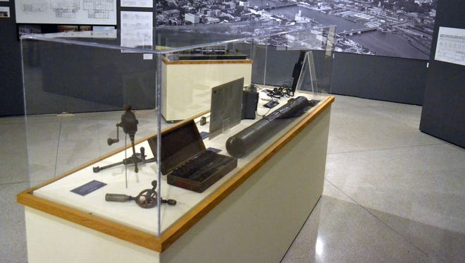 """Original drawings, artifacts and even a large aerial photograph of downtown Green Bay from 1960, visible in the back, are included in the new """"Building our Community: 100+ Years of Architecture and Design in Brown County"""" exhibit at Neville Public Museum in Green Bay."""