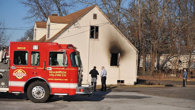 A fire is investigated after a building on the North Pearl Street lot of Fine Cars Inc. burned Monday, Feb. 29, 2016 in Bridgeton.