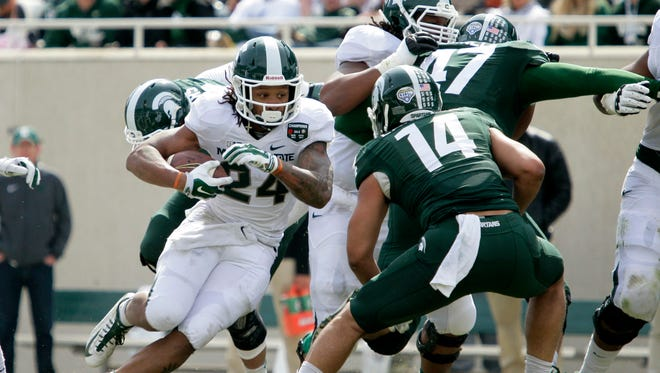 Michigan State White team's Gerald Holmes (24) rushes against the Green team's Chris Laneaux (14) during the NCAA college football team's scrimmage, Saturday, April 25, 2015, in East Lansing, Mich.
