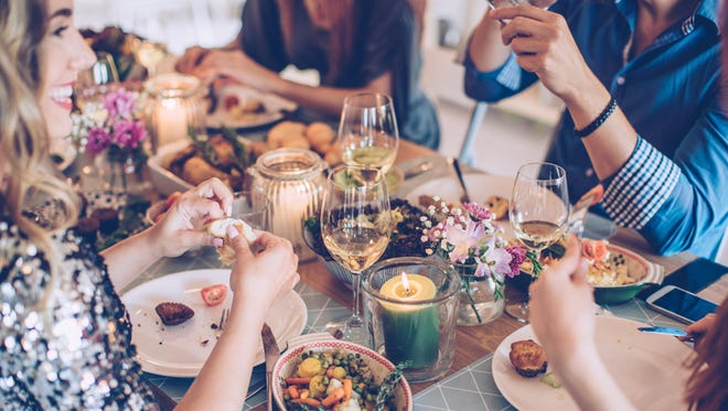 Friends having dinner party at home. It is a feast of food of all color and they are enjoy in every moment of the evening. They are happy and well dressed. Home is decorated with festive string lights and candles. Evening or night.