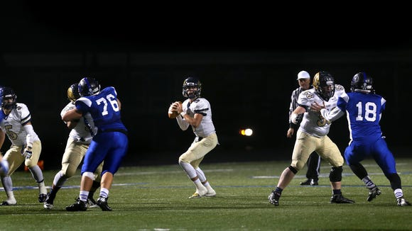 Decatur Central High School quarterback Tommy Stevens gets good protection to look downfield from teammates Austin Walker, defending Franklin's Jacob Lamping, left, and Josh Denney, guarding Nik Welch at right in the Hawks' 27-23 win at Franklin on Friday, October 17, 2014. At far left is Hawks defender Dakota Sidwell.