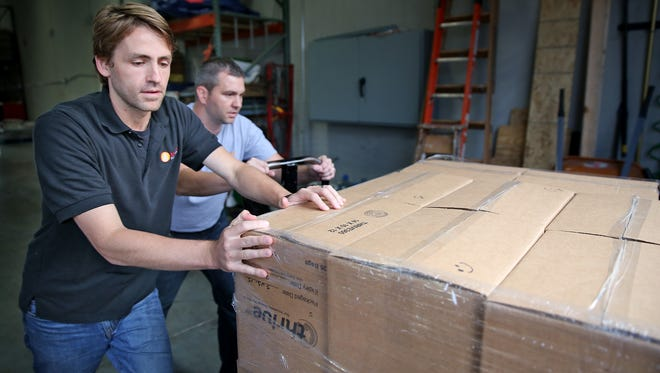 Jeremy Baynai, left, with Midwest Food Bank, and Shane Scarlett, with Thrive360, move boxes of packaged meals, at the Thrive360 warehouse, Tuesday, October 8, 2015.  Pellets of the Thrive360 packaged meals are being sent to South Carolina flood victims.  Midwest Food Bank is transporting the pellets to South Carolina.