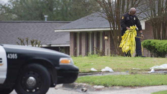 A police officer pulls up police tape after a fatal shooting on the 3100 block of Crawford Street in Montgomery, Ala. Police are investigating the death as a Homicide.