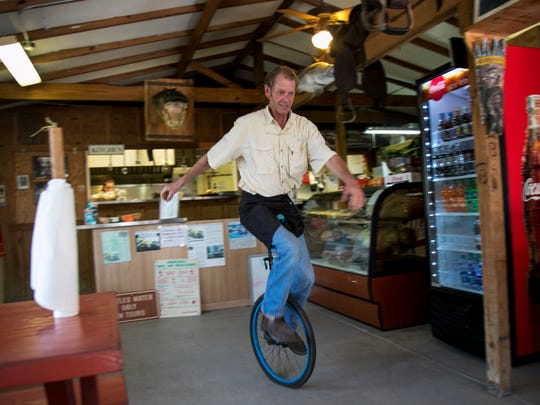 Chef John Anderson rides his unicycle through the Gator Shack restaurant during a break at Babcock Ranch Gator Shack.