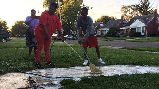 Neighbors Shantrice Riley, left, Kentneeta Keith and Antonio Williams clean blood off the walkway Thursday, Aug. 28, 2014, after four people were shot in front of his house on Detroit's northeast side.