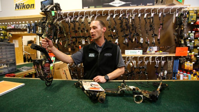 Nathan Asiu, store manager of the Farmington  Sportsman's Warehouse, talks on Wednesday at the store about various bows the store will feature at the Four Corners Outdoor and Travel Expo this weekend at McGee Park in Farmington.