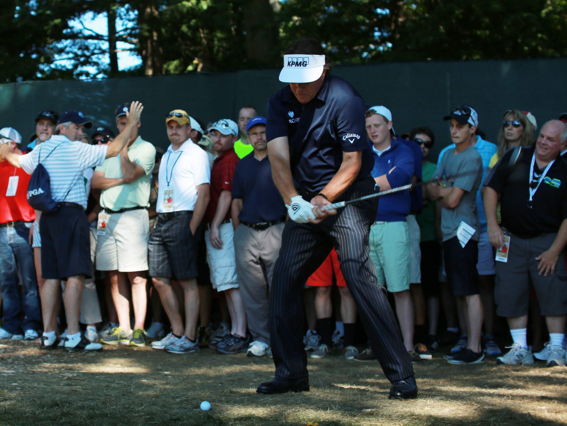 Phil Mickelson plays form the trampled-down rough on the 9th hole.
