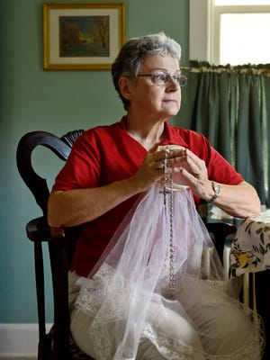 """Susan Blum holds her First Communion veil and her maternal grandmother's rosary for a portrait Wednesday, July 20, 2016, at Blum's New Freedom home. Blum, 63, said she was sexually assaulted by a clergy member in the Archdiocese of Boston when she was 15. A New Freedom resident since 1988, Blum had attended St. John the Baptist Catholic Church for years, but left in March after clergy in the Diocese of Harrisburg were required to read aloud a letter that opposed a Pennsylvania legislative bill that would drop a 30-year statute of limitations on when criminal sex-abuse charges can be filed. """"They don't understand they're protecting the Captain Underpants around the corner,"""" said Blum. """"I'm not anti-Catholic. I have loved my church, but I cannot in good conscience walk into a church building ever again."""""""