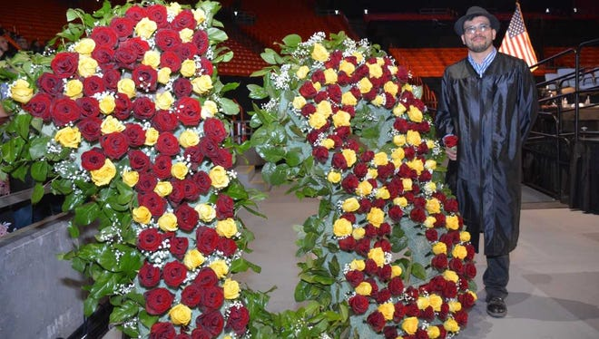 Gadsden High teacher Ramon Quiroga stands by the floral display he created for the 2018 graduation commencement ceremonies held May 26 at the Don Haskins Center in El Paso.